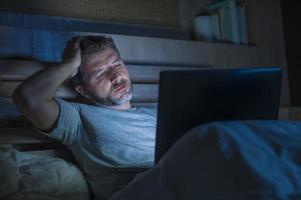 Attraktiver müder und gestresster Workaholic-Mann, der spät in der Nacht erschöpft auf dem Bett arbeitet und mit einem Laptop beschäftigt ist, der sich schläfrig und überarbeitet fühlt