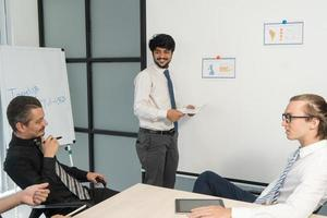 fröhlicher Geschäftstrainer, der lächelt, während er mit Mitarbeitern spricht foto