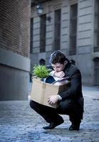 frustrierter Geschäftsmann auf der Straße mit Pappkarton abgefeuert foto