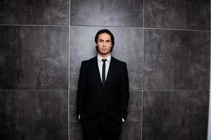 schöner reicher Geschäftsmann im schwarzen Smoking auf grauem Hintergrund