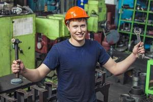 Der junge Mann arbeitet in der alten Fabrik an der Installation foto