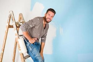 Maler in Farbe bespritztes Hemd, das eine Wand malt foto