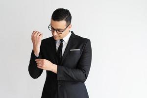 ernsthafter modischer junger Geschäftsmann, der Jackenmanschette zuknöpft foto