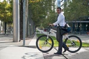 positiv aktiver Manager mit Fahrrad zur Arbeit gehen foto