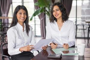 zwei glückliche Kolleginnen, die im Café mit Dokumenten arbeiten foto