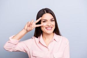 Porträt der verspielten, funky, netten, hübschen, charmanten Frau in guter Laune gestikulierendes V-Zeichen mit zwei Fingern nahe dem Auge, das Kamera lokalisiert auf grauem Hintergrund betrachtet