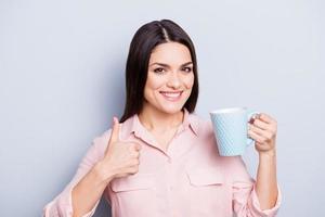Porträt der positiven, hübschen, charmanten, trendigen Frau, die Tasse mit Kaffee in der Hand gestikuliert Daumen oben wie Zeichen, das Kamera betrachtet, die auf grauem Hintergrund lokalisiert