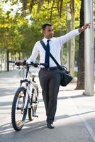 hispanischer Büroangestellter mit Fahrrad, das Hand anhebt foto