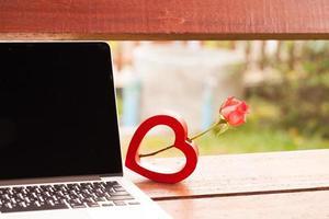 rote Herzen und eine Rosen auf hölzernem, Valentinstaghintergrund.