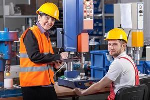 Produktionsmitarbeiter am Arbeitsplatz und Vorgesetzter foto