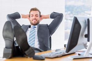 entspannter Geschäftsmann, der mit Beinen auf Schreibtisch sitzt foto