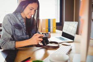 Grafikdesigner, der Bilder in der Digitalkamera betrachtet foto