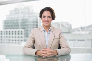 zufriedene Geschäftsfrau, die Kamera an ihrem Schreibtisch betrachtet foto