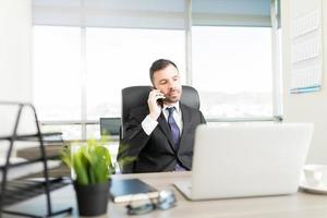 Geschäftsmann mit Smartphone am Arbeitsplatz foto