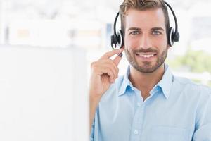 Porträt eines jungen Mannes mit Headset unter Verwendung des Computers foto