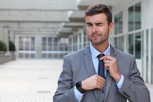 eleganter Geschäftsmann zwinkert, während er seine Krawatte justiert foto