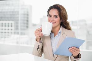 schöne zufriedene Geschäftsfrau, die Tablette verwendet, die Kaffee trinkt foto