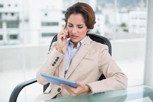 ernsthafte Geschäftsfrau auf einem Anruf, der Tablette hält foto