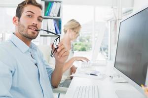 lächelndes lässiges junges Paar, das am Computer arbeitet foto