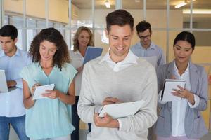 Gelegenheitsboss, der vor seinem Team steht und sich Notizen macht foto