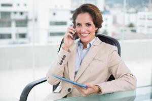 glückliche Geschäftsfrau, die mit Smartphone anruft foto