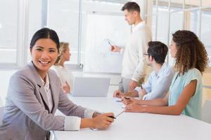 lässige Geschäftsfrau, die während des Treffens in die Kamera lächelt