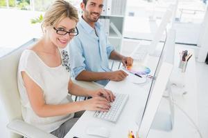 lässiges junges Paar, das an Computern arbeitet foto