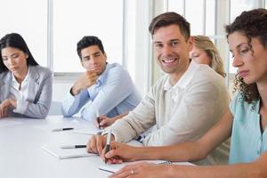 lässiger Geschäftsmann, der Kamera während des Treffens lächelt