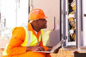 afrikanischer Elektriker, der computergestützten Maschinenstatus prüft foto