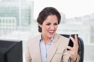 wütende Geschäftsfrau, die Smartphone anschreit foto