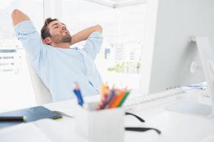 lässiger Mann, der mit Händen hinter Kopf im Büro ruht foto