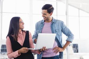 glückliche Geschäftskollegen mit Laptop im Büro foto