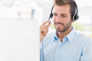 Nahaufnahme eines zufälligen jungen Mannes mit Headset unter Verwendung des Computers foto