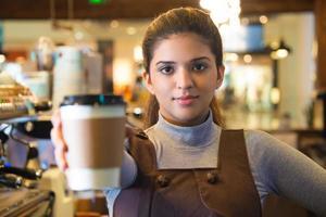 selbstbewusster junger weiblicher Kaffee-Barista, der Tasse gibt foto
