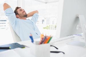 lässiger junger Mann, der mit Händen hinter Kopf im Büro ruht foto