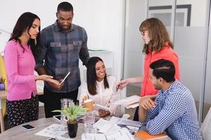 lächelnde Geschäftsleute, die am Schreibtisch diskutieren foto