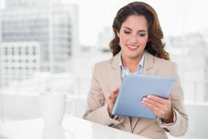 schöne lächelnde Geschäftsfrau mit Tablette foto