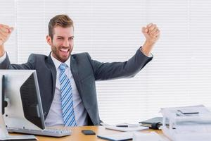 fröhlicher Geschäftsmann, der Faustcomputer am Schreibtisch zusammenpresst foto