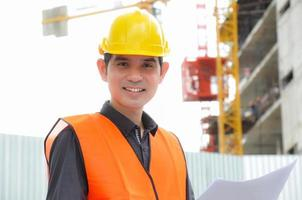 asiatischer Ingenieur oder Vorarbeiter vor der Baustelle foto