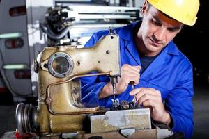 Mechaniker repariert Industrienähmaschine foto