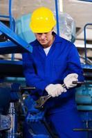 junger Mechaniker, der Fabrikmaschine repariert