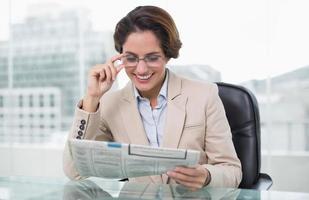 lächelnde Geschäftsfrau, die Zeitung an ihrem Schreibtisch liest foto