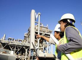 Zwei Ingenieure arbeiten in der Nähe eines Kraftturms foto