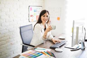 Geschäftsfrau, die Kaffee an ihrem Schreibtisch trinkt foto