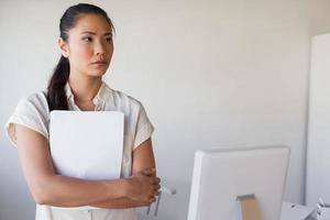 zufällige Geschäftsfrau, die Dokument beim Denken hält foto