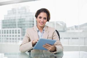 Geschäftsfrau lächelt und hält ihren Tablet-PC foto