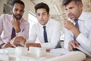 Drei männliche Kollegen diskutieren über ein Architekturmodell foto