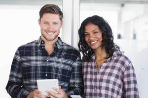Porträt von lächelnden Geschäftskollegen, die digitales Tablett halten foto