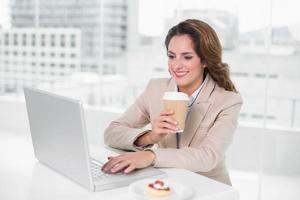Geschäftsfrau, die Kaffee an ihrem Schreibtisch mit Laptop trinkt foto