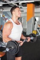 fröhlicher junger männlicher Athlet trainiert mit Langhantel foto